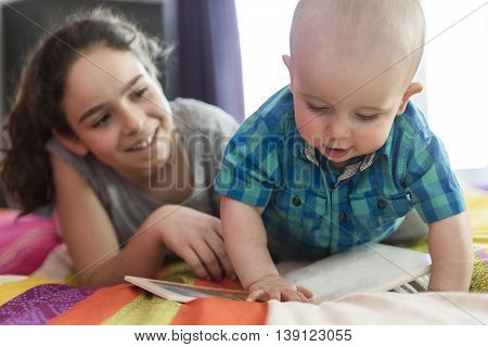 The elder sister reads the book to the brother.