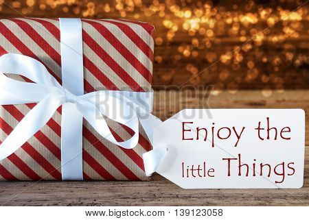 Macro Of Christmas Gift Or Present On Atmospheric Wooden Background. Card For Seasons Greetings, Best Wishes Or Congratulations. White Ribbon With Bow. English Quote Enjoy The Little Things