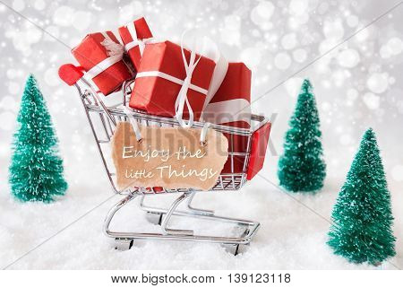 Trollye With Christmas Presents Or Gifts. Snowy Scenery With Snow And Trees. Sparkling Bokeh Effect. Label With English Quote Enjoy The Little Things