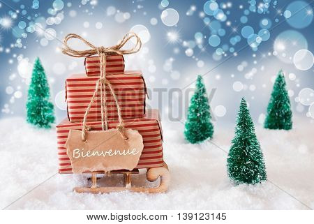 Sleigh Or Sled With Christmas Gifts Or Presents. Snowy Scenery With Snow And Trees. Blue Sparkling Background With Bokeh Effect. Label With French Text Bienvenue Means Welcome