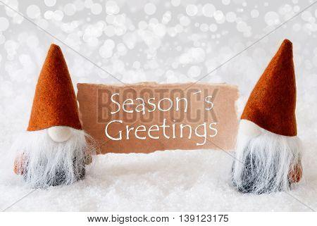 Christmas Greeting Card With Two Bronze Gnomes. Sparkling Bokeh Background With Snow. English Text Seasons Greetings