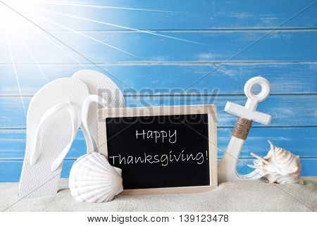 Chalkboard With English Text Happy Thanksgiving. Blue Wooden Background. Sunny Summer Card With Holiday Greetings. Beach Vacation Symbolized By Sand, Flip Flops, Anchor And Shell.