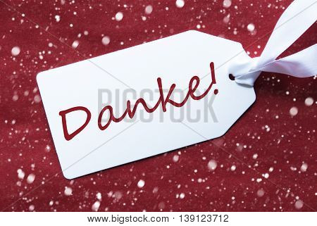 One White Label On A Red Textured Background. Tag With Ribbon And Snowflakes. German Text Danke Means Thank You