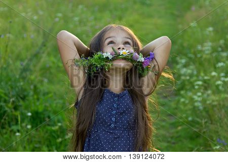 Happy cute little girl with long flowing hair and a wreath of wildflowers laughing on the summer meadow