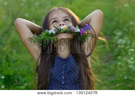 Happy cute little girl with long flowing hair and a wreath of wildflowers laughing with her hands behind head on the summer meadow