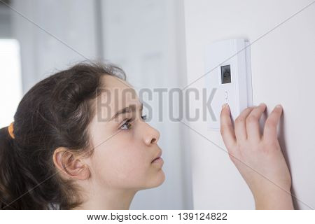 A Teen Adjusting Thermostat On Central Heating Control