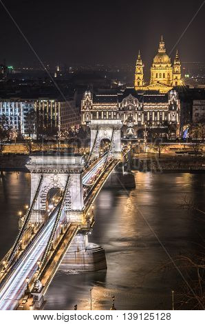 Night View of Chain Bridge over Danube River and St. Stephen's Basilica in Budapest Hungary. As Seen from Royal Palace in Buda Castle.