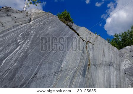 Slice the raw surface of white and grey marble in the natural environment. Marble career and the place of its production. Background stone, industrial material for making buildings and interior.