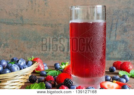 fresh cold summer berries juice in a glass with ripe berries in a wicker bowl and around