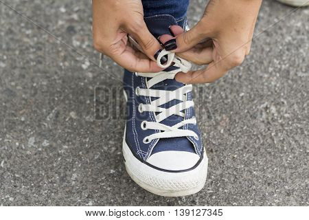 Hands girl with beautiful manicure knotted the laces on your shoelace.