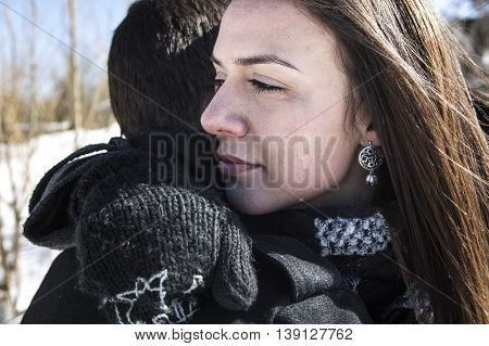 A Woman crying near man in winter and wiping tear off her face