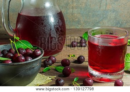cold cherry juice in a glass and pitcher on wooden table with ripe berries in pottery bowl