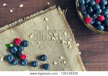 fresh healthy ingredients. oat flakes blueberry raspberry blackberry for breakfast yogurt or smoothie on canvas and in wicker bowl on wooden table. vintage effect