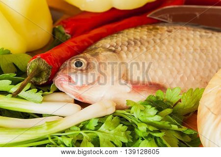 Crucian fish with green vegetables, red chili close up , prepared for cooking dinner home