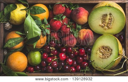 Healthy summer fruit variety. Melon, sweet cherries, peach, strawberry, orange and lemon on wooden tray background, top view, horizontal composition