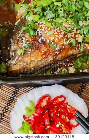 Seafood. Close up view of the fresh fried fish in a frying pan with sause and chili. Home cooking