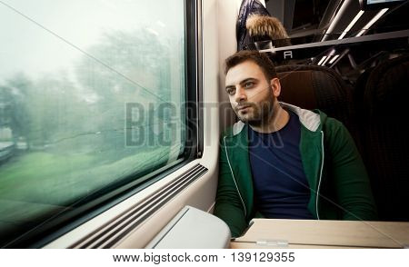 Young man staring out the train window on a rainy and grey day.