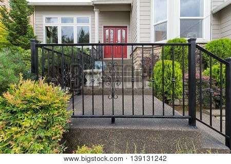 House front entrance with wrought iron railings on stairs with plants landscaping