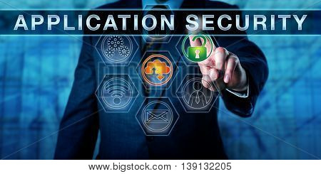 Businessman is pushing APPLICATION SECURITY on an interactive control screen. Computer security and information technology concept. Business metaphor. Close up torso shot of manager in blue suit.