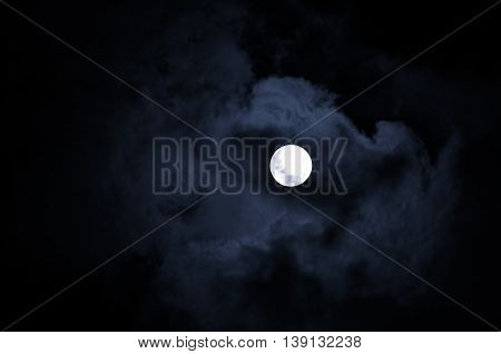 Night mysterious landscape in cold tones - full moon in the night sky and dramatic night clouds. Night sky background in Halloween style with full moon