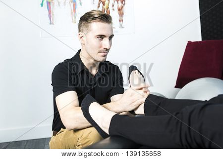 A Osteopath doing reflexology massage on female foot