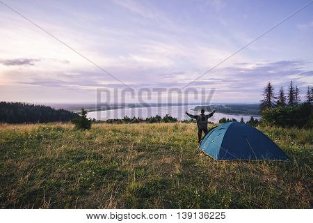 Hiker meets good morning with raised hands just got out from his tent.