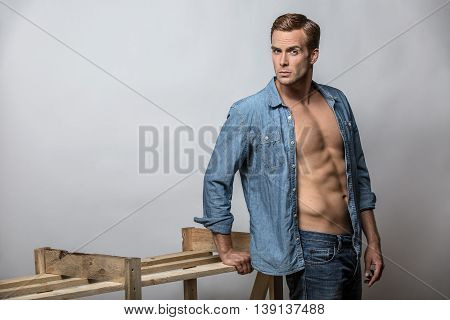 Athletic guy in a blue denim unbuttoned shirt and blue jeans stands in the studio on the gray background. He looks into the camera while leans on a wooden construction. Horizontal.
