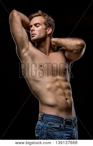 Strong man in blue jeans with naked torso stands with closed eyes on the black background in the studio. He holds his hands on the neck behind the head. Vertical low-key photo.
