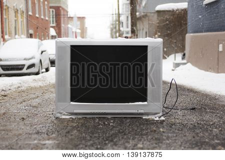An old TV left on the street on winter season