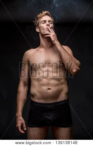 Young man with muscular body in black underpants stands on the black background in the studio. He smoke a cigarette and holds it with left hand. Vertical low-key photo.