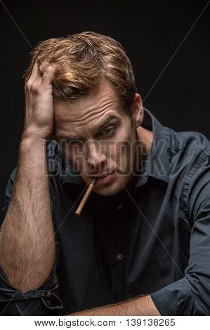 Pensive man in dark shirt with a cigarette in the mouth on the black background in the studio. He holds the right hand on his head and looks down. Vertical low-key photo.
