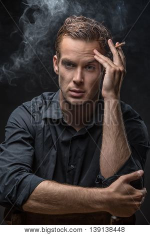 Attractive guy in dark shirt sits on a chair on the black background in the studio. He holds a cigarette in left hand and looks in front of himself. Smoke swirls around man. Vertical low-key photo.