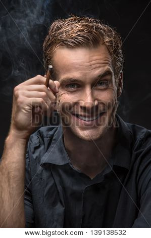 Smiling guy in dark shirt on the black background in the studio. He holds a cigarette in the right hand and looks into the camera. Smoke swirls around him. Vertical low-key photo.