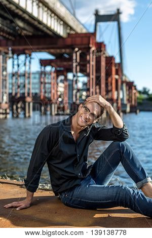 Attractive barefoot guy in glasses sits on the quay on the background of the river and the bridge. He wears blue jeans and a dark shirt. Man looks into the camera with a smile. Outdoors. Vertical.