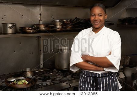Female Chef Standing Next To Cooker In Restaurant Kitchen