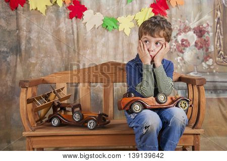 The boy in the studio thought playing with wooden toy cars.