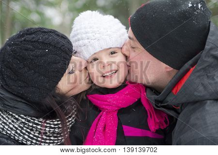 A Portrait of kissing mother father and baby in winter park