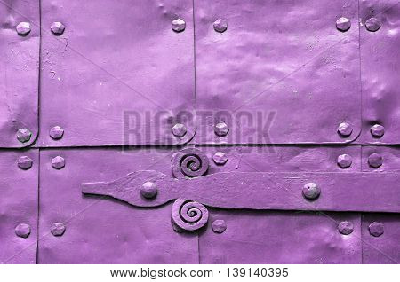Metal light pink surface of old hammered metal plates with metal rivets and architectural details on them. Metal pink industrial background.