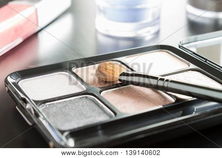 Woman cosmetics include brush and palette and eyeshadow and lip gloss on black floor