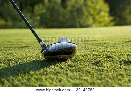 A selective focus low angle view of a golf driver ready to hit a teed up ball