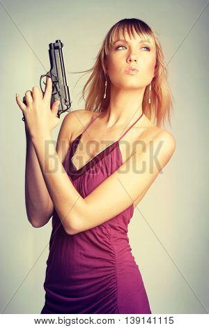 Beautiful blond spy, woman holding gun