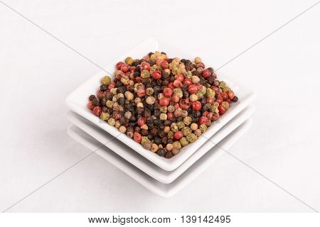 Colorful peppercorns in a white mixing bowl. Horizontal cut with white background.