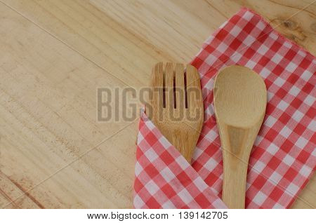 Wooden kitchen utensils and fabric on wooden background