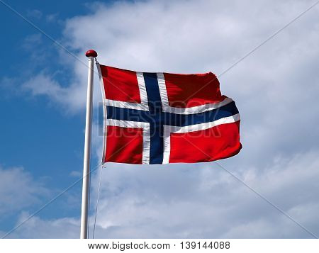 Waiving flag of Norway with partly cloudy blue sky background
