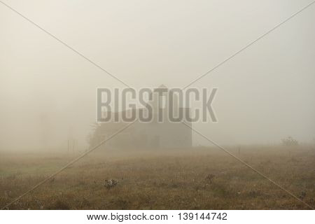 rural landscape with deserted old house in the fog