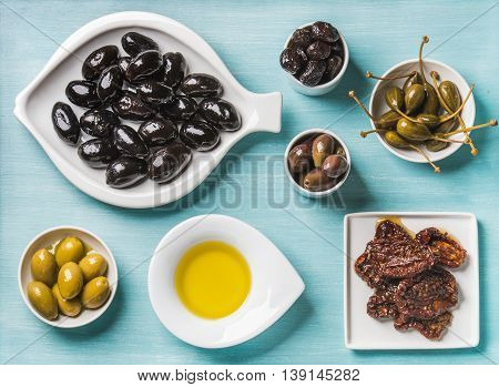 Mediterranean snack assortment. Black and green Greek olives, capers, olive oil and sun-dried tomatoes over turquoise blue background, top view