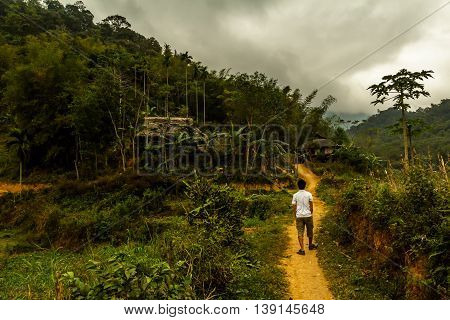 A man walks through the green Vietnamese countryside on a stormy day