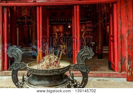 Incense burns in front of a red buddhist temple in Vietnam