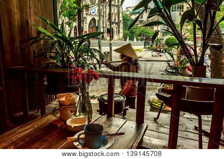 A Vietnamese vendor carries baskets past a cafe in Hanoi
