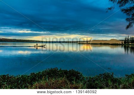 A man on a small boat gliding across a glassy blue lake under a blue sky at twilight in Vietnam